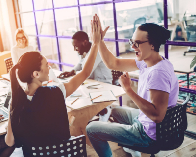 Two coworkers doing a high five showing high performance teams